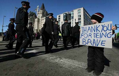In 2009, this child held a sign as police officers walk in a funeral procession for Cst. Eric Czapnik of the Ottawa Police Service. The sign read: Thank you for being brave.