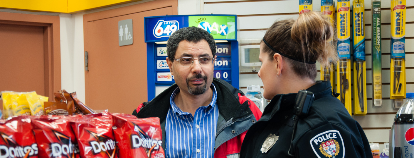 Convenience store clerk speaking with a police officer.