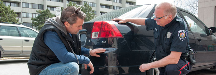 An officer assists a member of the public with his collision reporting.