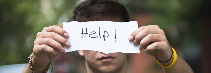 "Teenager holding up a ""Help"" sign"