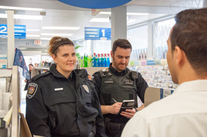 Officers speaking to a Pharmacist about robbery prevention.