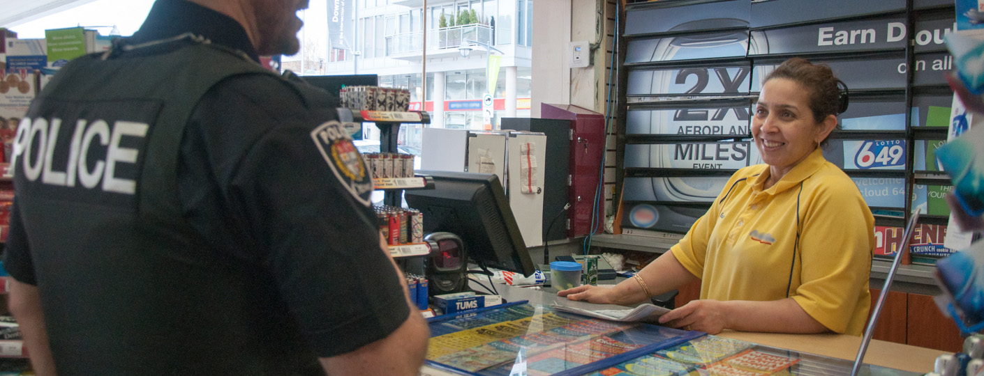 Police officer speaking a convenience store clerk about crime prevention.