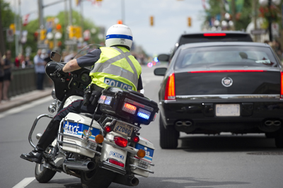 Police officer on a motorcycle in traffic in Ottawa.