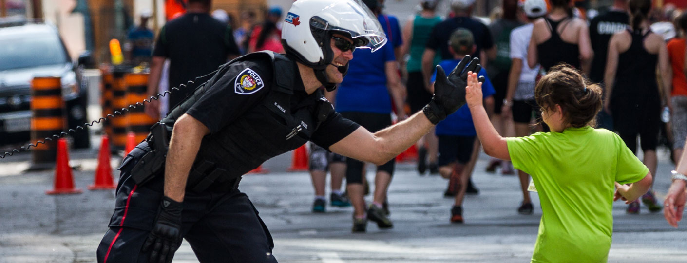 Sergeant Martin Groulx high-fiving young child in Ottawa Race Weekend's kids marathon