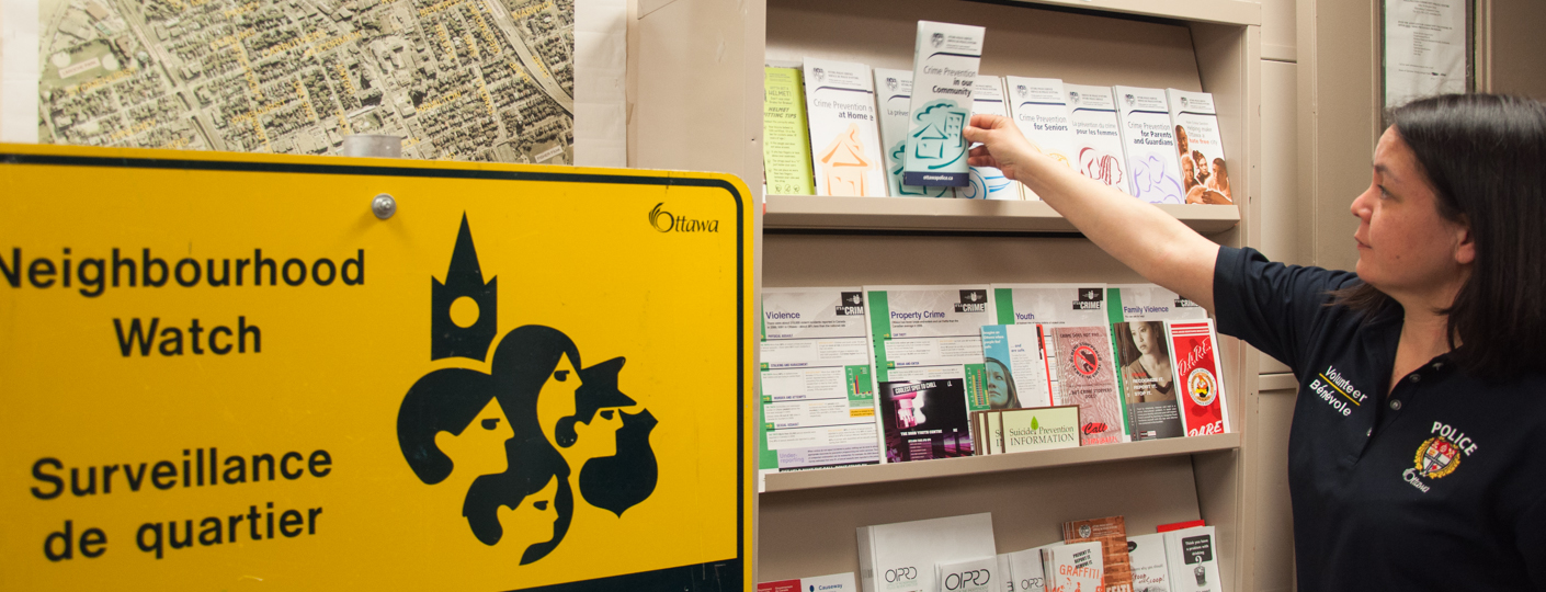 A volunteer taking a pamphlet off the shelf.