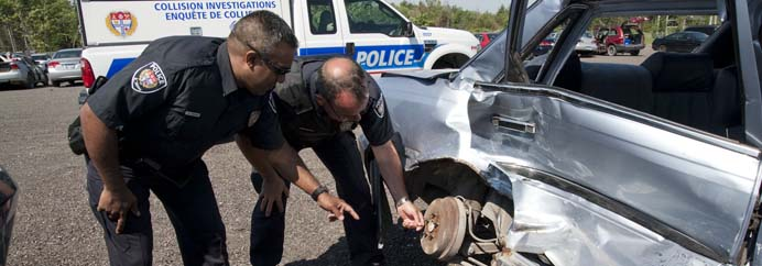 police officers looking at damage to a car
