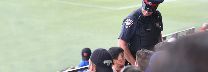 Police Officer at a baseball field, looking down at a child.