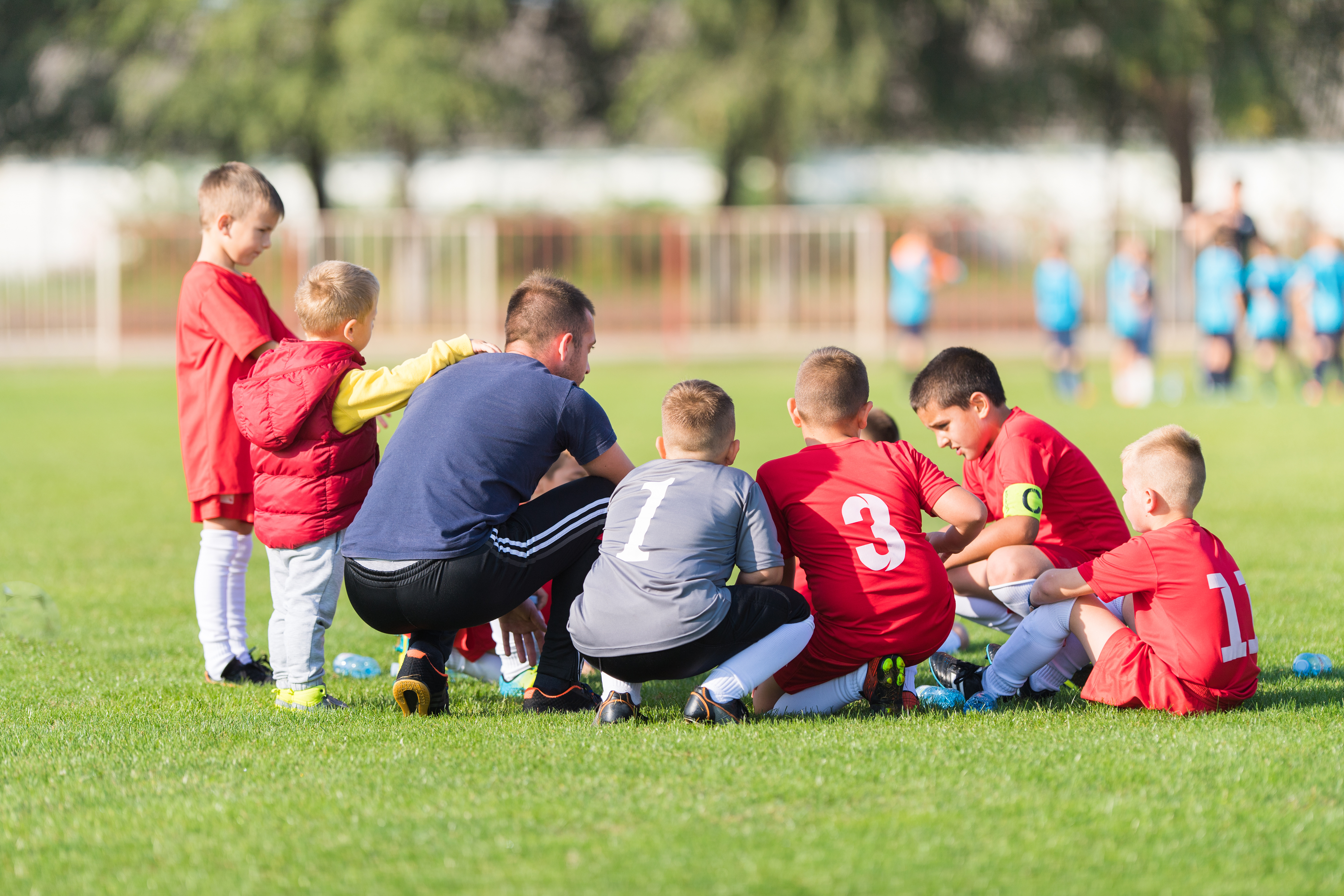 Soccer coach talking to a team of children