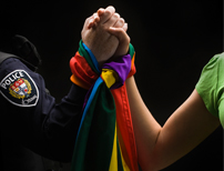 hands clutched together with rainbow flag
