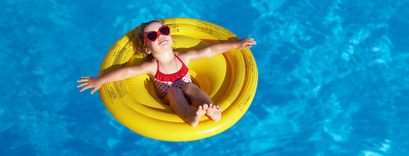 Toddler in a swimming pool with adult within arms reach