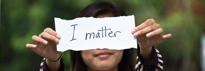 Girl holding a sign that reads: I matter.
