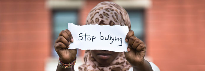 Teen girl holding up a sign that reads: stop bullying.