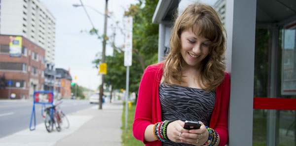 A young woman texting on her phone while waiting for the bus.