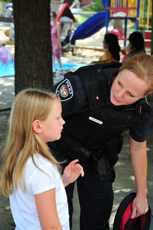 Police Officer speaking to a child in the park