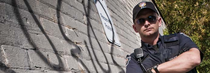Officer leaning against a graffitied wall.