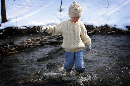 Child playing in a creek during the Spring.