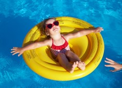 Girl in a pool with parent at arms length.