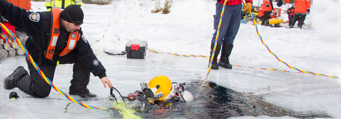 Ottawa Police Officer from Marine Dive Unit being lowered into icey waters.