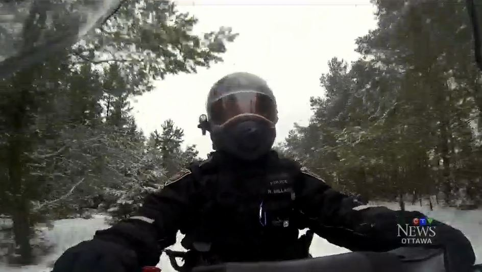 police officer driving a snowmobile